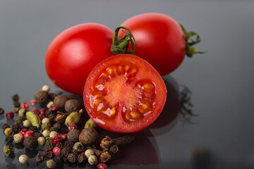 Cherry tomatoes on a glass black background with various spices. Seasoning and tomato