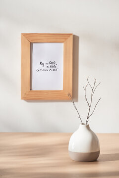 Still life with vase and photo frames on wooden table over white background