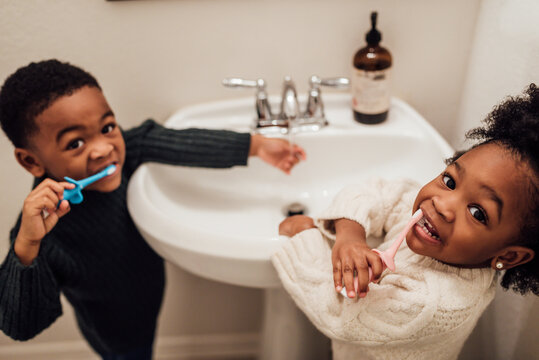 Brother and Sister brushing teeth in bathroom