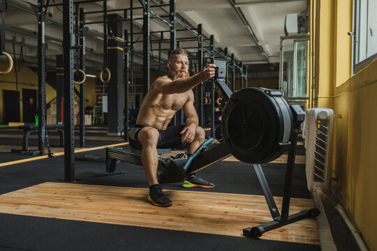 Strong and healthy man working out on a rowing machine, inside a crossfit gym.