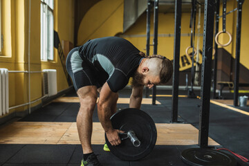 Strong and healthy man workin out with bar and weights inside a crossfit gym.