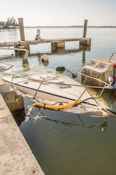 Miami, Florida - September 16, 2017: Sunken boat on Brickell Bay avenue marina days after hurricane Irma strikes the city during hurricane season.