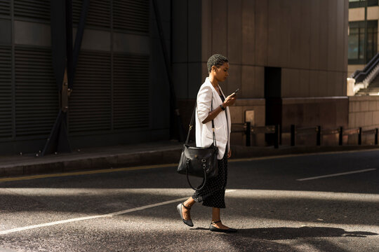 Young Businesswoman going at work, walking during a sunny day.
