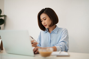 Shot of an thinking asian woman using a mobile phone and laptop