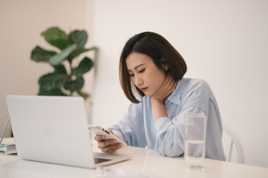 Thinking asian woman using a mobile phone and laptop