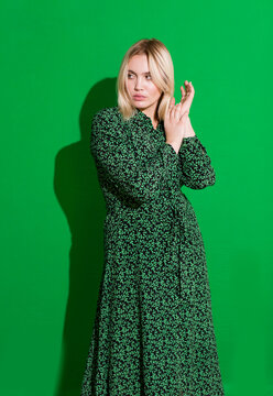 Beautiful blonde plus size woman in green dress on green background