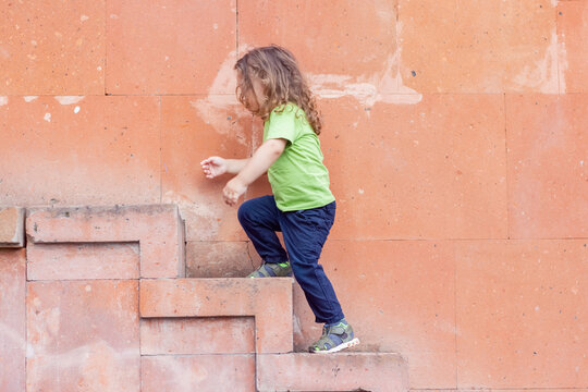 portrait of a little long hair boy near the wall on stairs