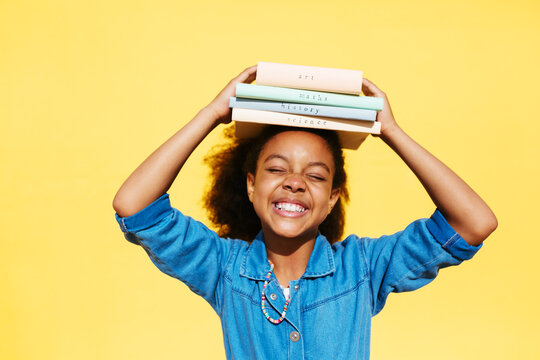 Happy African American girl balancing books on head