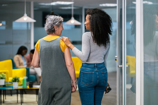 rear view of a curly hair woman walking with a senior woman at t