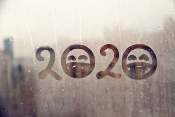 hahdmade painted numbers 2020 with sad face with closed eyes in protective medical mask on splashed by rain foggy glass on blue window, concept photo self-isolation, coronavirus, covid - 19