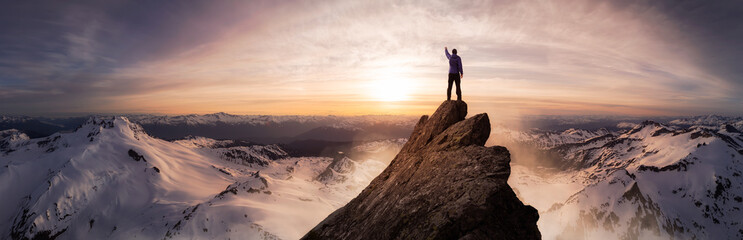 Magical Fantasy Adventure Composite of Man Hiking on top of a rocky mountain peak. Background Landscape from British Columbia, Canada. Sunset or Sunrise Colorful Sky