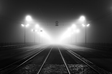 Tramway track and asphalt road (highway) through the illuminated empty Stone bridge in a thick fog...