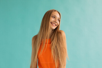 Content teen blonde smiling on turquoise background