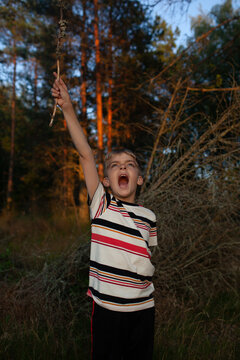 A boy plays expressively at dusk in rural Finland.