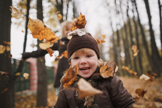 Little laughing girl in front of her throwing autumn leaves in park