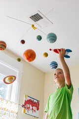 Happy Child in Bedroom Astronaut Playing with Toy Rocket Ship and Solar System Mobile