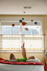 Child Astronaut Lying on Bed with Toy Rocket Ship and Solar System Mobile