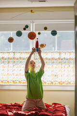 Child Astronaut Playing with Toy Rocket Ship and Solar System Mobile
