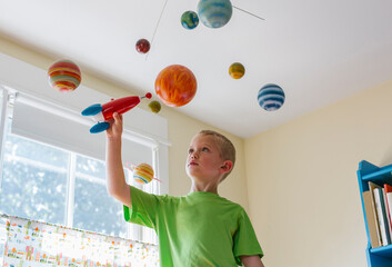 Future Astronaut Playing with Toy Rocket Ship and Solar System Mobile