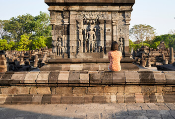 Foto op Canvas Historisch mon. Back view of woman looking at a hindu carving in Prambanan Temple, Java, Indonesia