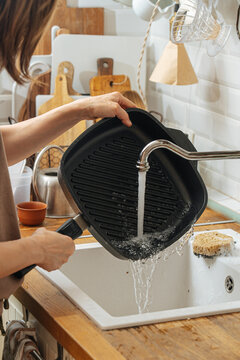 Woman washing grill pan in sink
