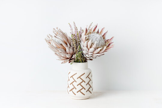 Beautiful floral arrangement including beautiful dried pink King Proteas and delicate thryptomene flowers, in a stylish aztec vase.