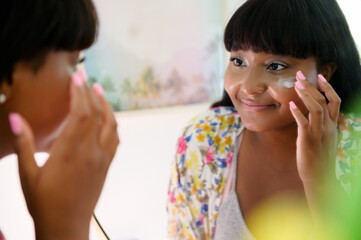 Women applying cream to face in mirror