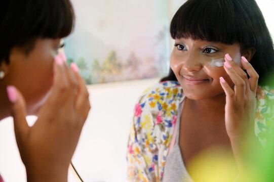 Women applying cream to face in mirror