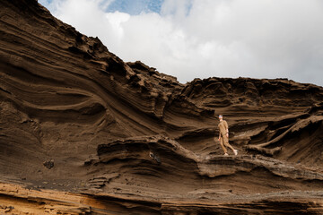 Woman in brown on rocky hill with different wave and shapes.