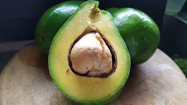An avocado cut in half with two hole avocadoes in the background
