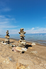 Baikal Lake at sunny day. Sandy beach with tourists stone pyramids on the shore of Olkhon Island. Natural background. Summer travel