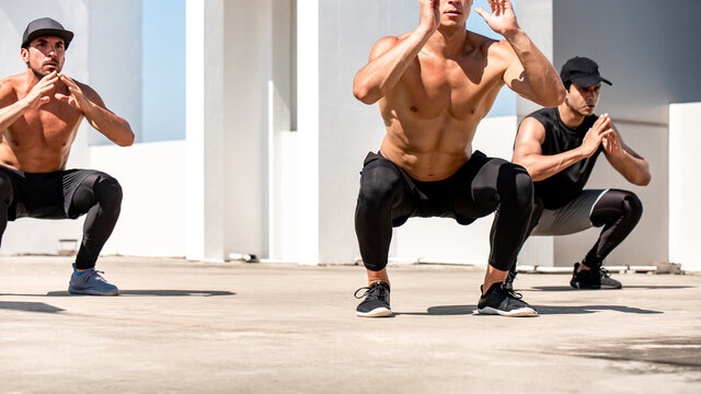 Group of fit sports men doing squat bodyweight workout training outdoors on building rooftop in sunlight