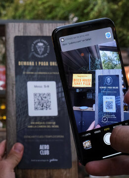 """A client using his mobile phone scans a QR code to place an order of a pizza with its ingredientes through the """"Funky Pay"""" app, which replaces waiters, at Funky Pizza restaurant in Palafrugell"""