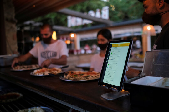 """Employees pick up the pizzas near an IPad with the """"Funky Pay"""" app, at Funky Pizza restaurant, where the app replaces waiters, in Palafrugell"""