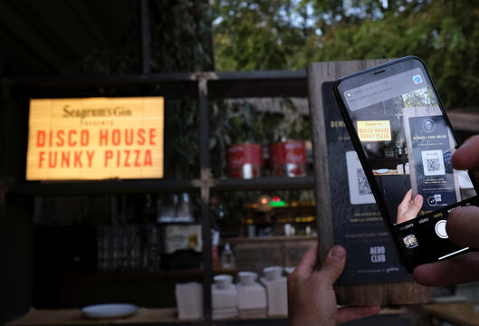 """Client uses his mobile phone scans the QR code to place your order of a pizza with its ingredientes through of the """"Funky Pay"""" app, where the app replaces waiters at Funky Pizza restaurant in Palafrugell"""