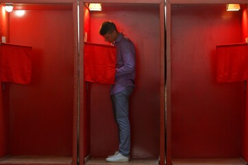 A man stands inside a voting booth during the early voting ahead of the presidential election in Minsk
