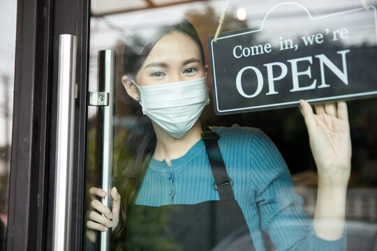Young female shopkeeper  is opening her shop with face mask on the face