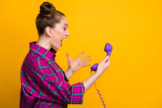 Profile photo of crazy angry furious lady two funny buns yell into cable telephone handset line bad connection can't speak boyfriend wear casual plaid shirt isolated yellow color background