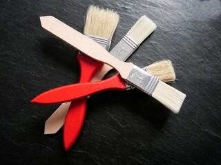 Rote und naturfarbene Farbpinsel gestapelt