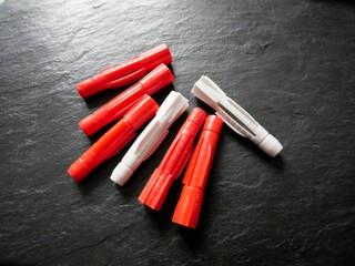 Weiße und rote Plastikdübel auf schwarzem Hintergrund