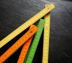 Verschiedenfarbige bunte Meterstäbe Zollstöcke vor schwarzem Hintergrund