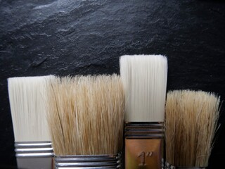 Farbpinsel mit Naturborsten in einer Reihe mit schwarzem HIntergrund