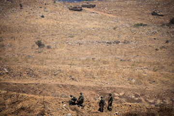 Israeli soldiers walk during a drill in the Israeli-controlled Golan Heights near the Israel-Syria frontier