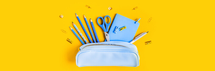 Web banner with School writing materials: pencils, scissors, notepad, pen case on yellow background.