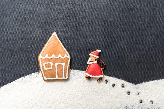 Lebkuchenhaus im Schnee mit Weihnachtsmann auf schwarzem Hintergrund