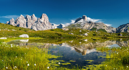 Awesome Nature Landscape. Alpine lake with crystal clear water and frash grass and flowers. Perfect Blue sky and mountains peaks. Incredible view of Dolomites Alps. Tre Cime di Lavaredo National park