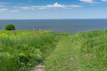 Spring landscape with an earth road leading down to Kakhovka Reservoir riverside located on the Dnipro River near Skelki village, Ukraine