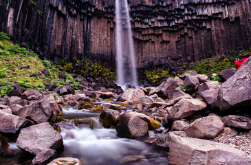 Amazing Nature landscape of Iceland. Svartifoss is one of the unique waterfalls with basalt columns and colorful sky during sunset. in South-Iceland. Vatnajokull National Park, Iceland, Europe.