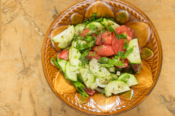 Top view on ceramic bowl full of vegan salad with red tomotoes, cucumbers, mangold , parsley  standing on a dirty wooden surface