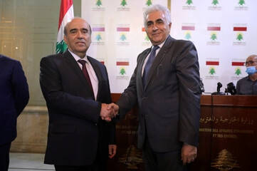 Hitti who resigned as foreign minister, shakes hands with Wehbe, Lebanon's newly appointed foreign minister at in Beirut